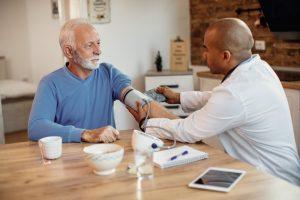 Older man sitting with doctor, getting his blood pressure taken