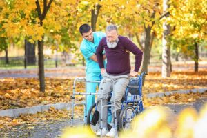 Male at-home nurse helping older man stand up from wheelchair