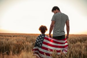Father and young daughter standing in field with American flag wrapped around them