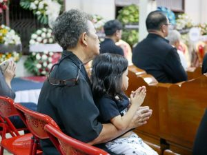 Grandmother holding granddaughter in her lap at a funeral