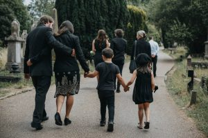 Family wearing black as they walk through cemetery