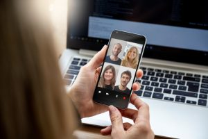 Woman holding smart phone in hand, on video call