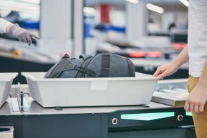 Shows man going through airport security with carry on bag