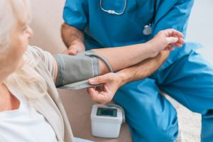 Shows nurse taking patient's blood pressure